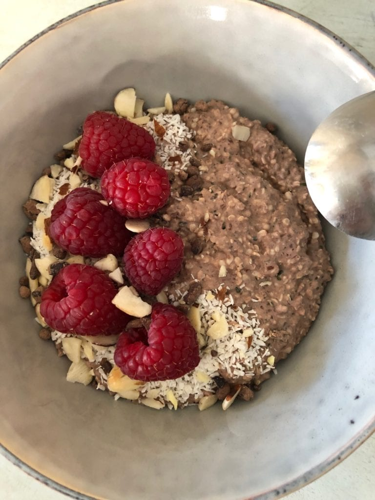 a white bowl filled with chocolate raspberry overnight breakfast porridge
