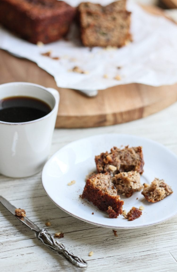 a half eaten piece of banana bread with a cup of coffee