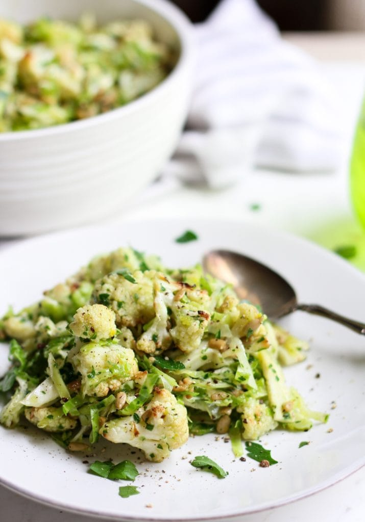 a white plate with roasted cauliflower brussels sprouts salad