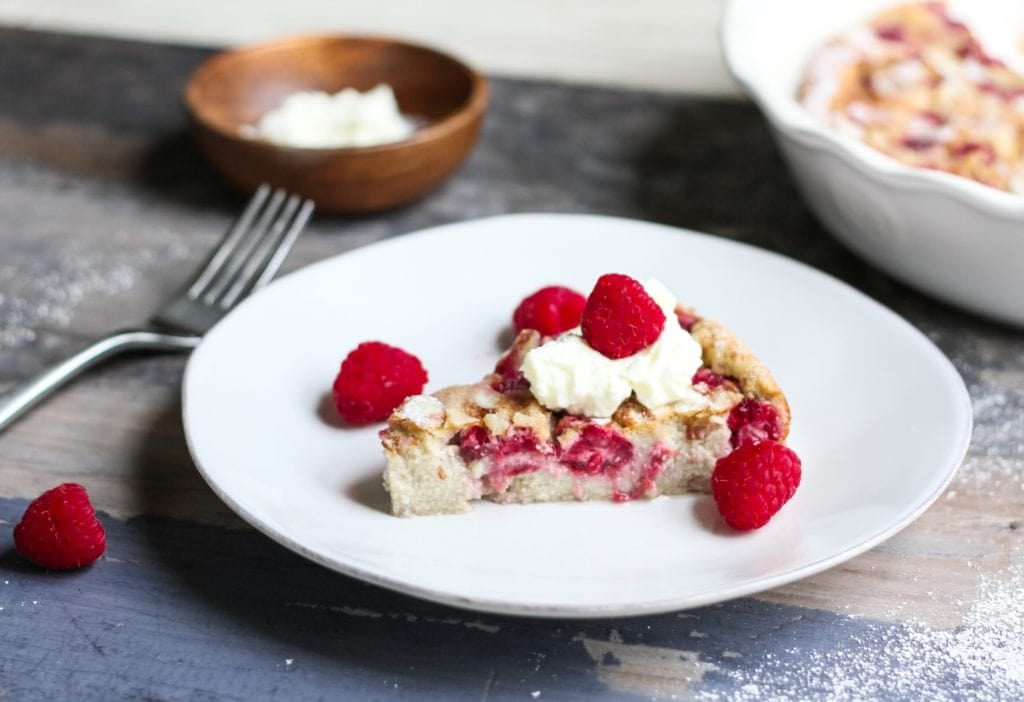 side view of a slice of raspberry flaugnarde on a white plate