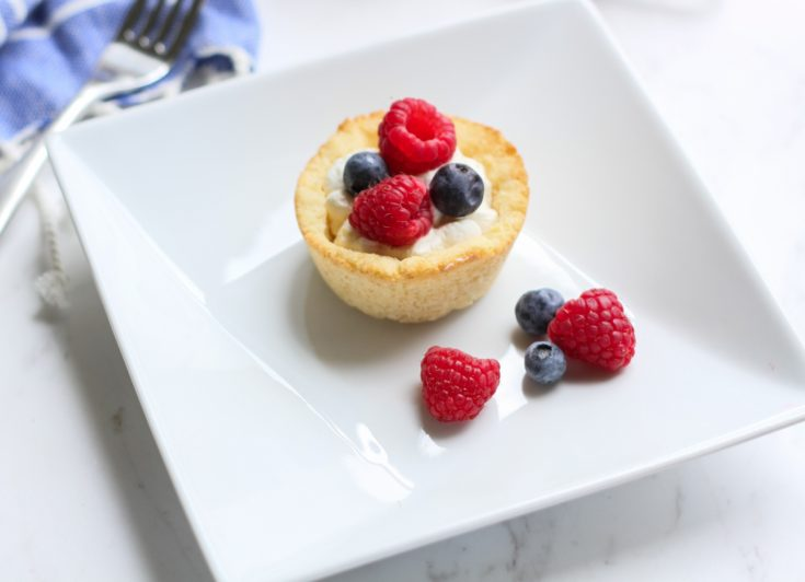 a sugar cookie cup filled with cheesecake and topped with berries