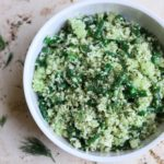 a white bowl full of cauliflower fennel feta pesto salad