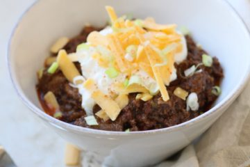 chili con carne in a white bowl with a spoon