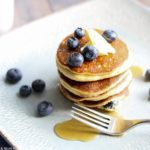 a stack o f lemon blueberry ricotta pancakes with blueberries and butter on a grey plate