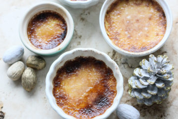 four ramekins with keto creme brulee on a marble counter top