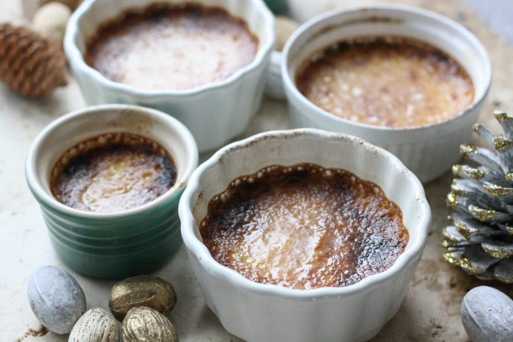 four ramekins filled with keto creme brulee on a beige marble counter