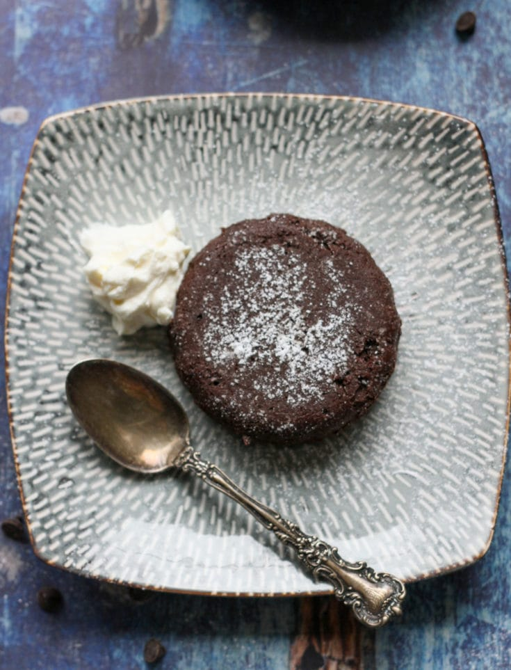 a molten chocolate lava cake on a blue plate with whipped cream