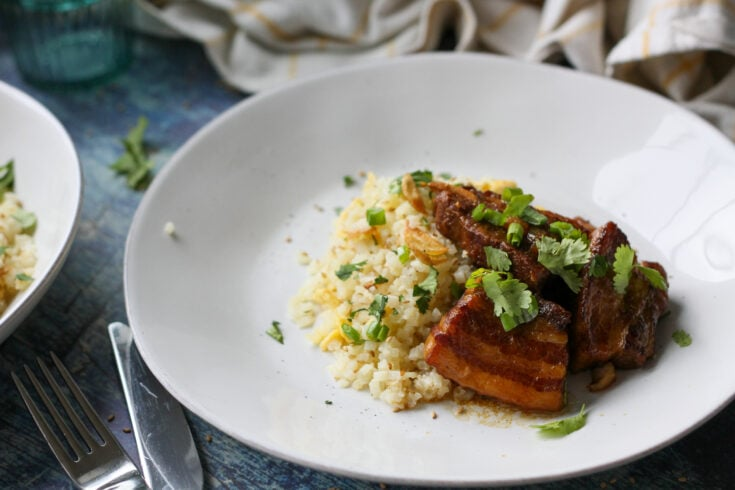 pork belly adobo with garlic cauliflower rice on a white plate