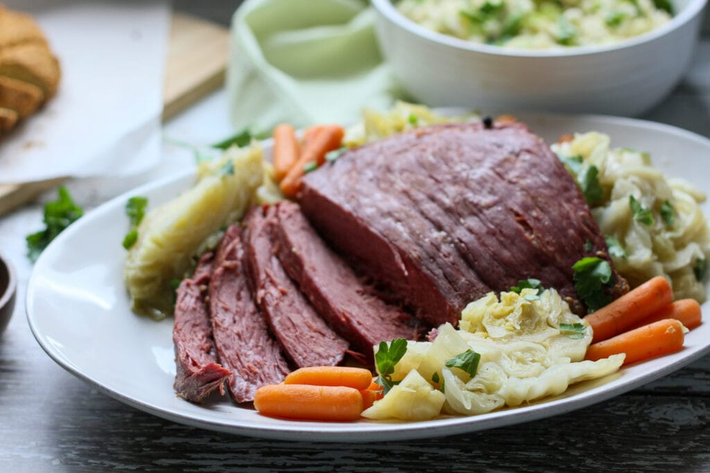 sliced instant pot corned beef and cabbage on a serving platter
