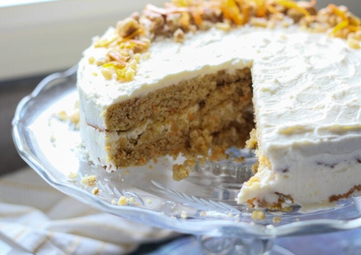 decorated low carb carrot cake with cream cheese frosting on a glass cake plate
