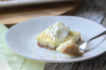 keto coconut lime bar topped with whipped cream on a white plate with a fork