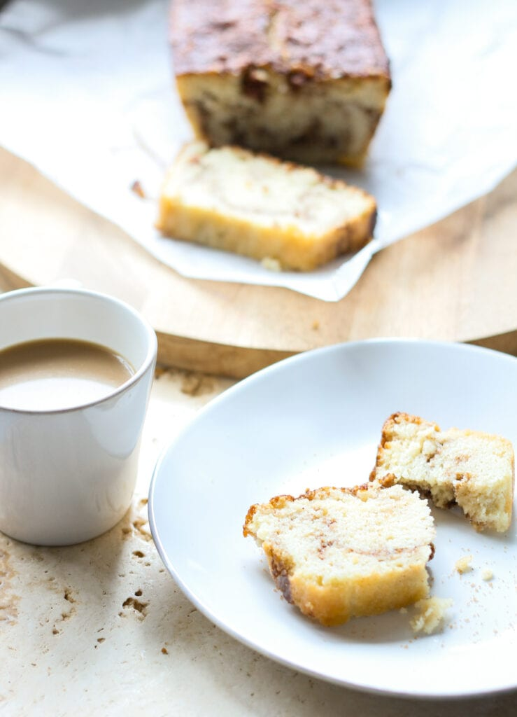 a slice of keto cinnamon bread on a plate with a cup of coffee