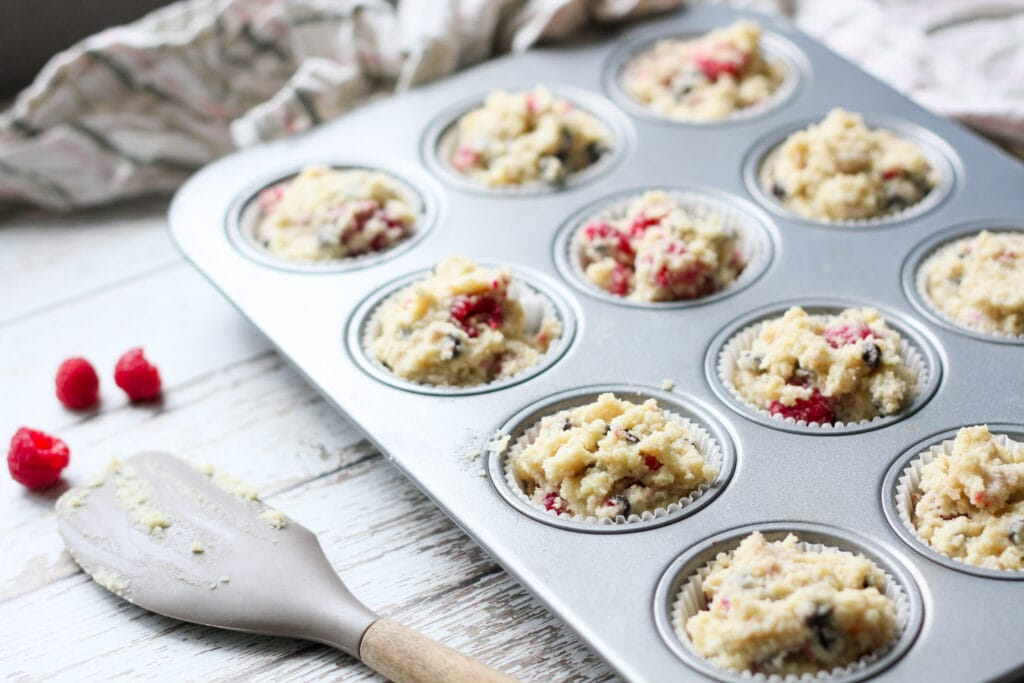 muffin tin filled with low carb raspberry chocolate chip muffin dough before baking