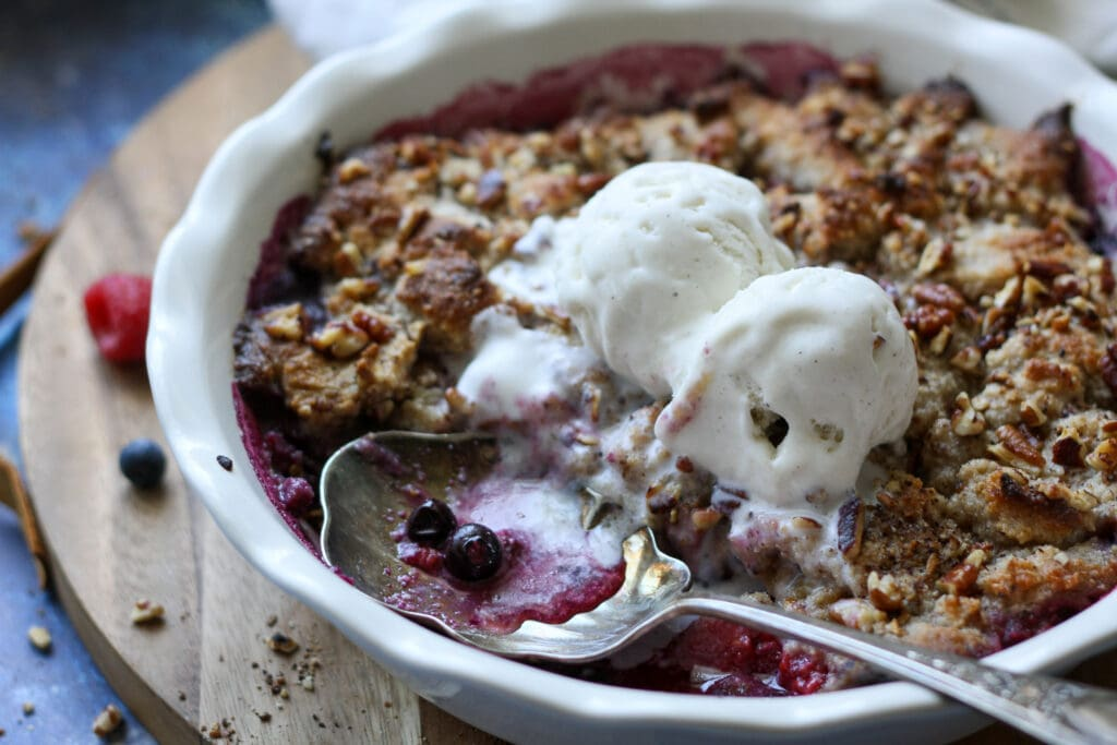 low carb mixed berry crisp topped with ice cream in a white dish