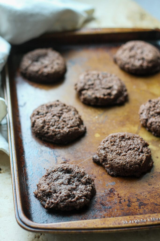 baked double chocolate chip brownie cookies cooling on a baking sheet