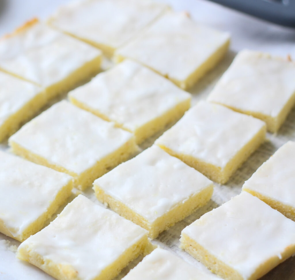 rows of low carb keto lemon brownies with lemon glaze on white parchment paper