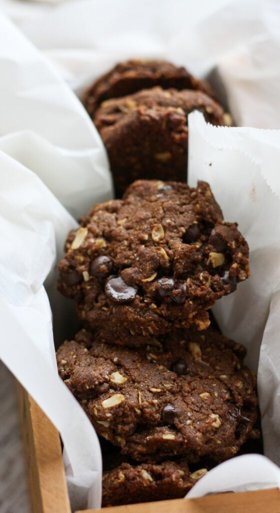 vegan oatmeal chocolate chip cookies packed in a wooden box with parchment paper
