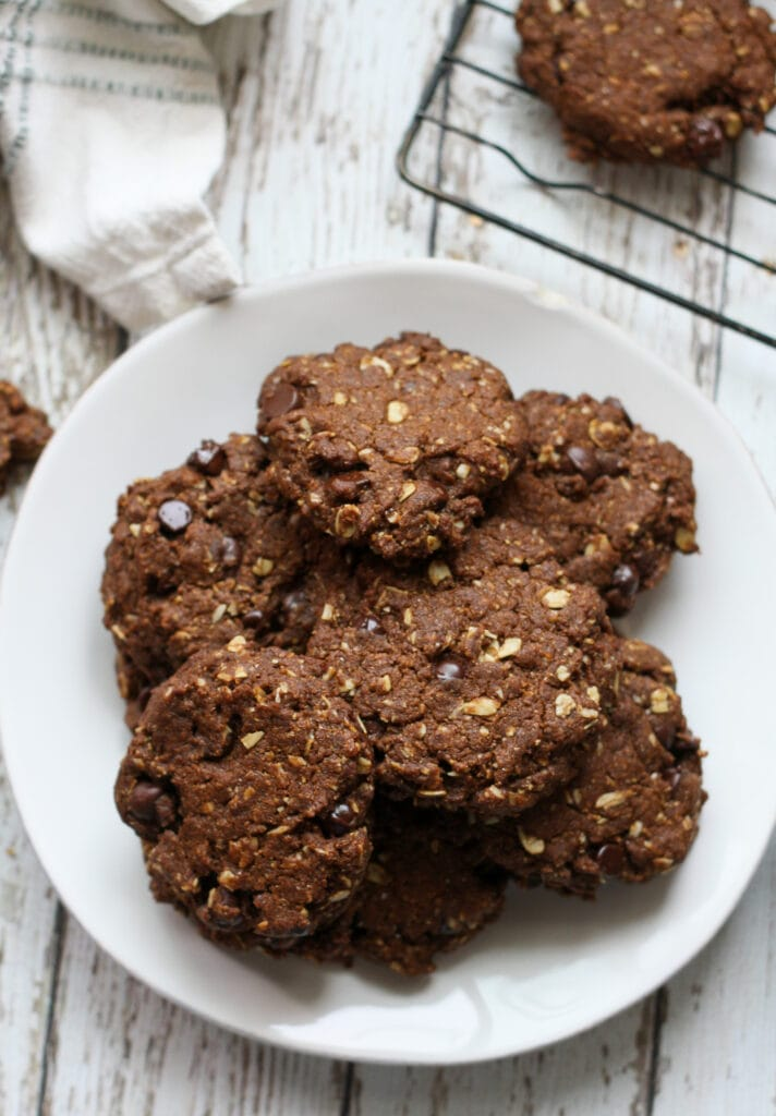 a pile of vegan oatmeal chocolate chip cookies on a white plate