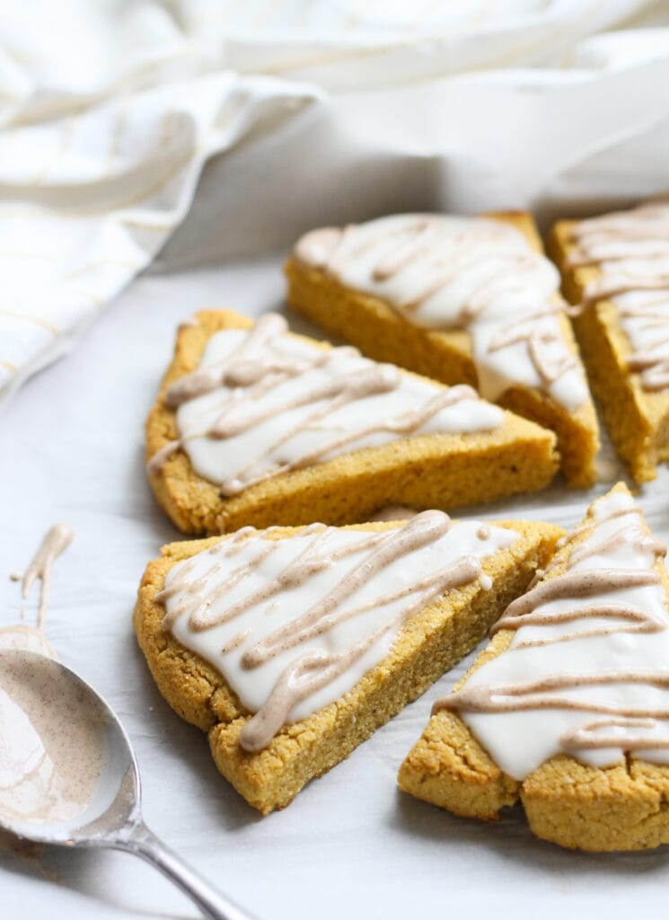 keto pumpkin scones with cinnamon spice glaze cooling on a baking tray