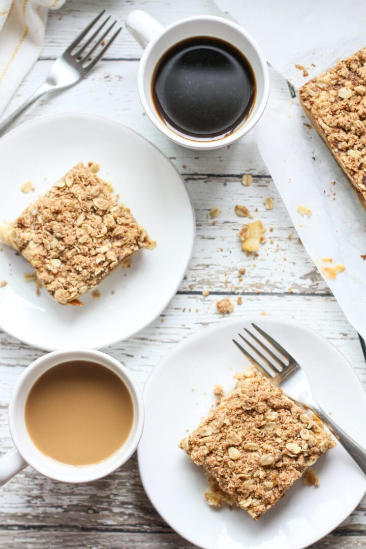 two slices of vegan apple coffee cake on white plates with cups of coffee