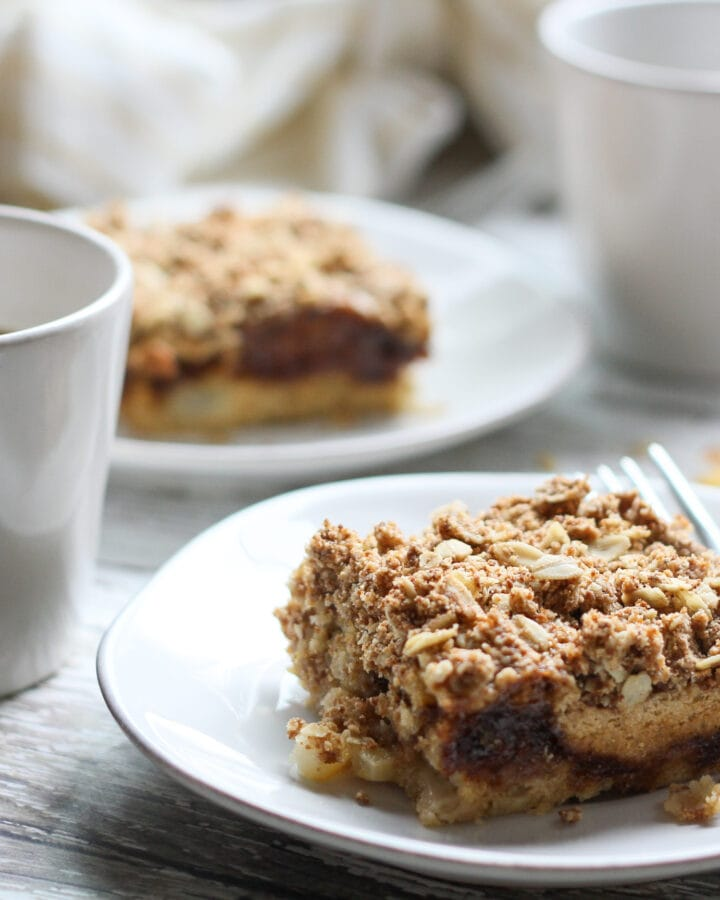 two slices of vegan apple coffee cake on a white plate with coffee