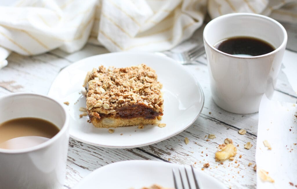 a slice of vegan apple coffee cake on a white plate with coffee