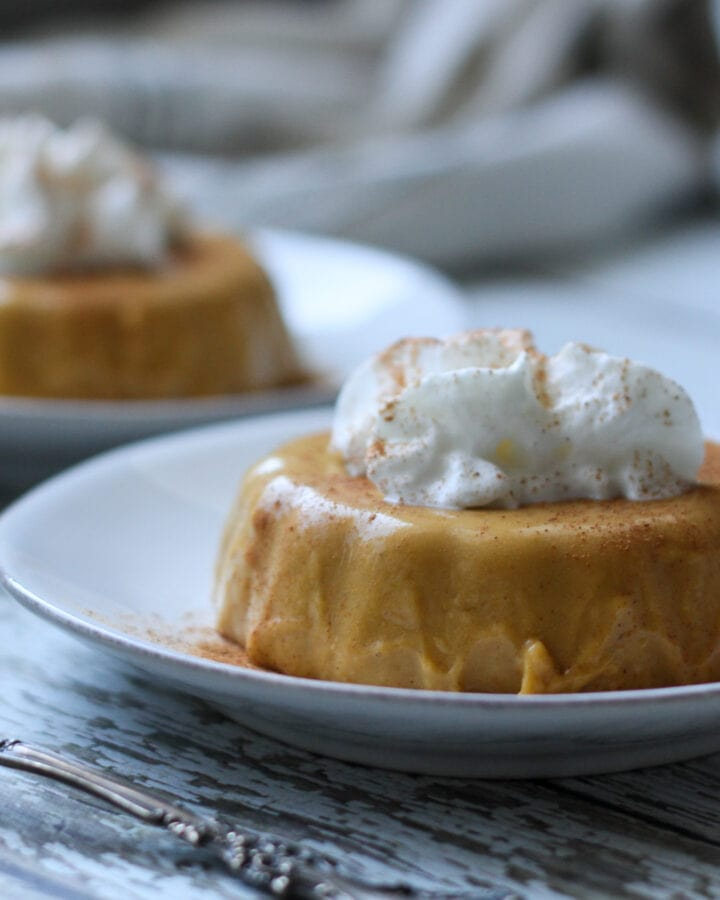 two keto pumpkin pie panna cotta on white plates with whipped cream