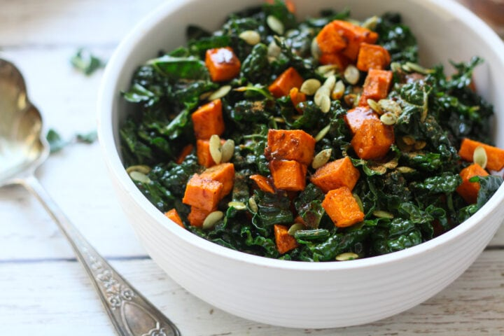 side view of roasted sweet potato and kale salad in a white serving bowl