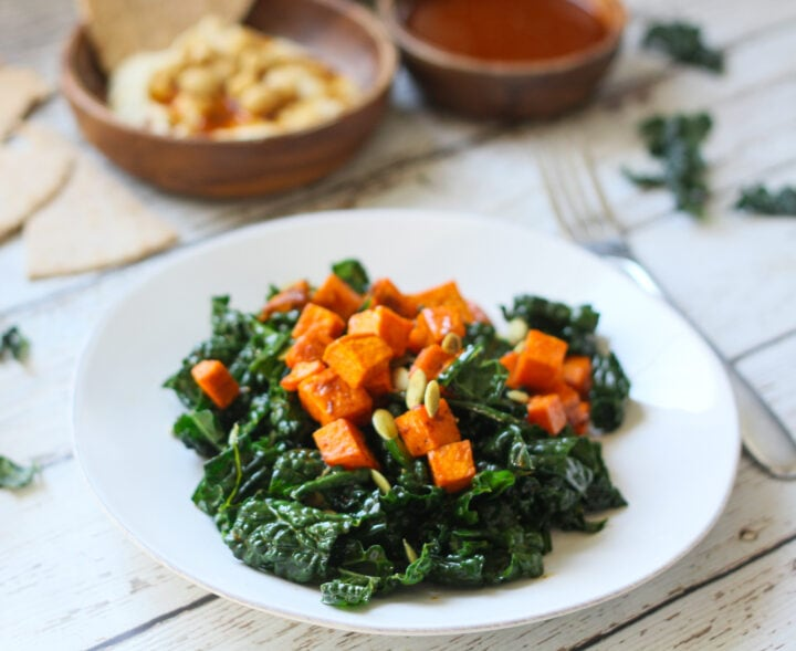 Roasted sweet potato and kale salad plated on a white plate with a small bowl of hummus and pita