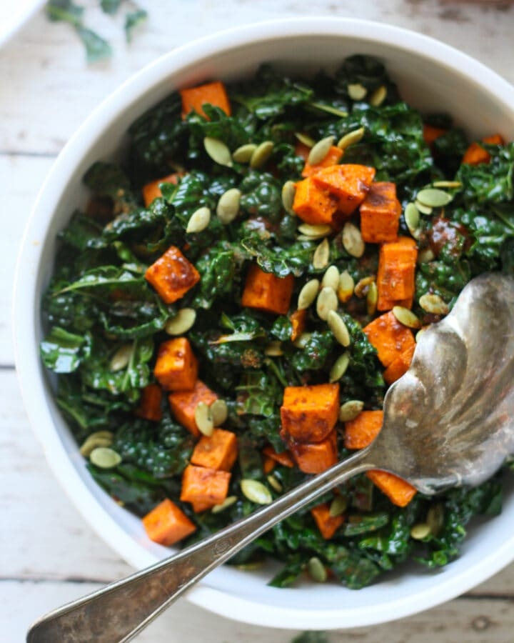 roasted sweet potato and kale salad in a white serving bowl with a spoon