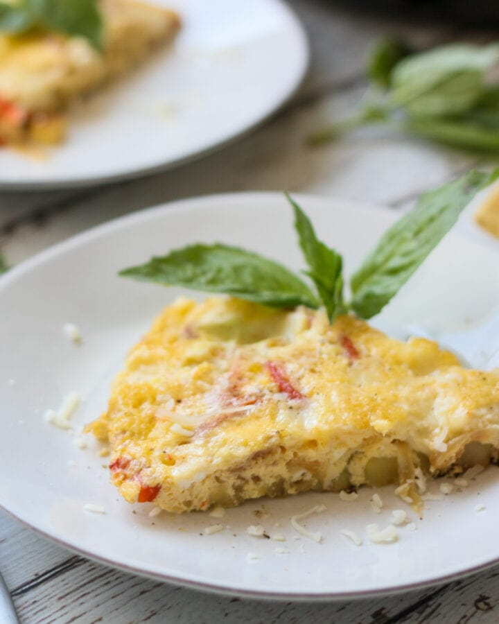 slice of red pepper and potato frittata on a white plate with fresh basil